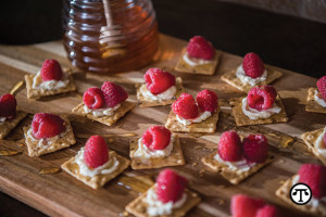 Harvest Stone® organic crackers are delicious topped with cream cheese, raspberries, and drizzled honey.